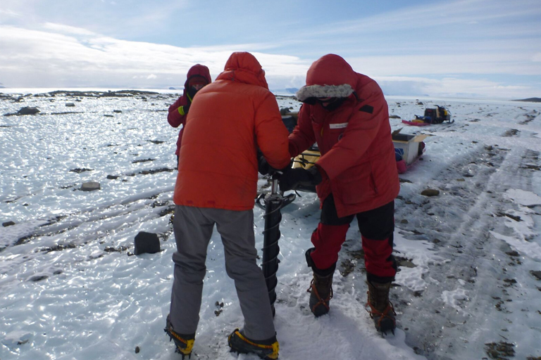People drilling a hole in ice.
