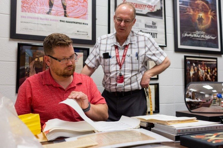 "Jason Aukerman, left, coordinator for development and programming at the Center for Ray Bradbury Studies at IUPUI, and Jon Eller, director of the center, examine some pages of Ray Bradbury's stage play script of ""Fahrenheit 451"" in the center. All photos by Liz Kaye, IU Communications"