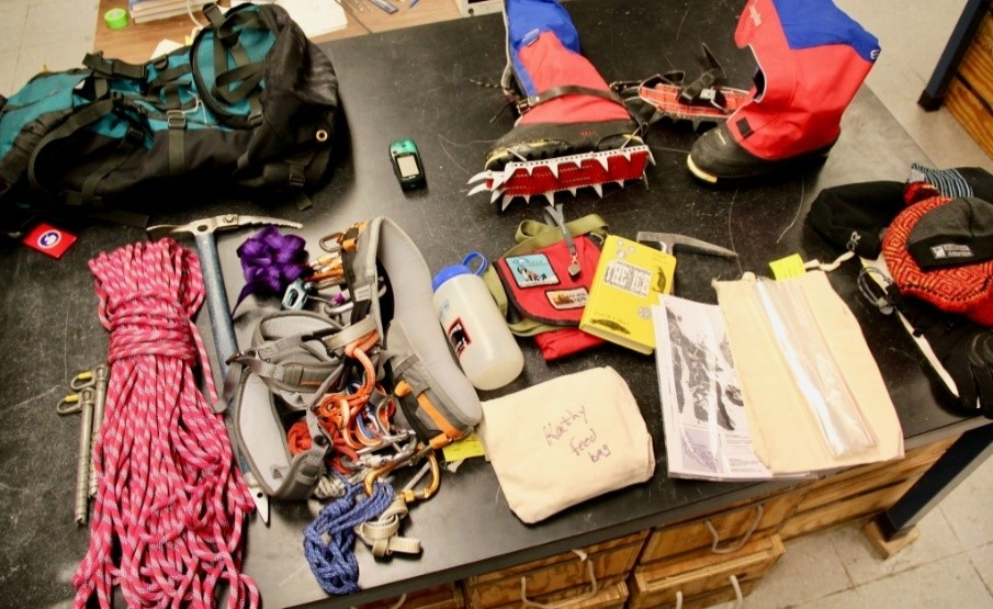IUPUI earth sciences professor Kathy Licht's field backpack, in the top left corner, is filled with necessities like a GPS and crampons for her mountaineering boots, shown top right. Other equipment includes, second row from left, ice screws, a climbing rope, an ice ax, a climbing harness, food and water supplies, a field book , a rock hammer, field maps, sample bags, and extra warm gear. Photo by Tim Brouk, IU Communications
