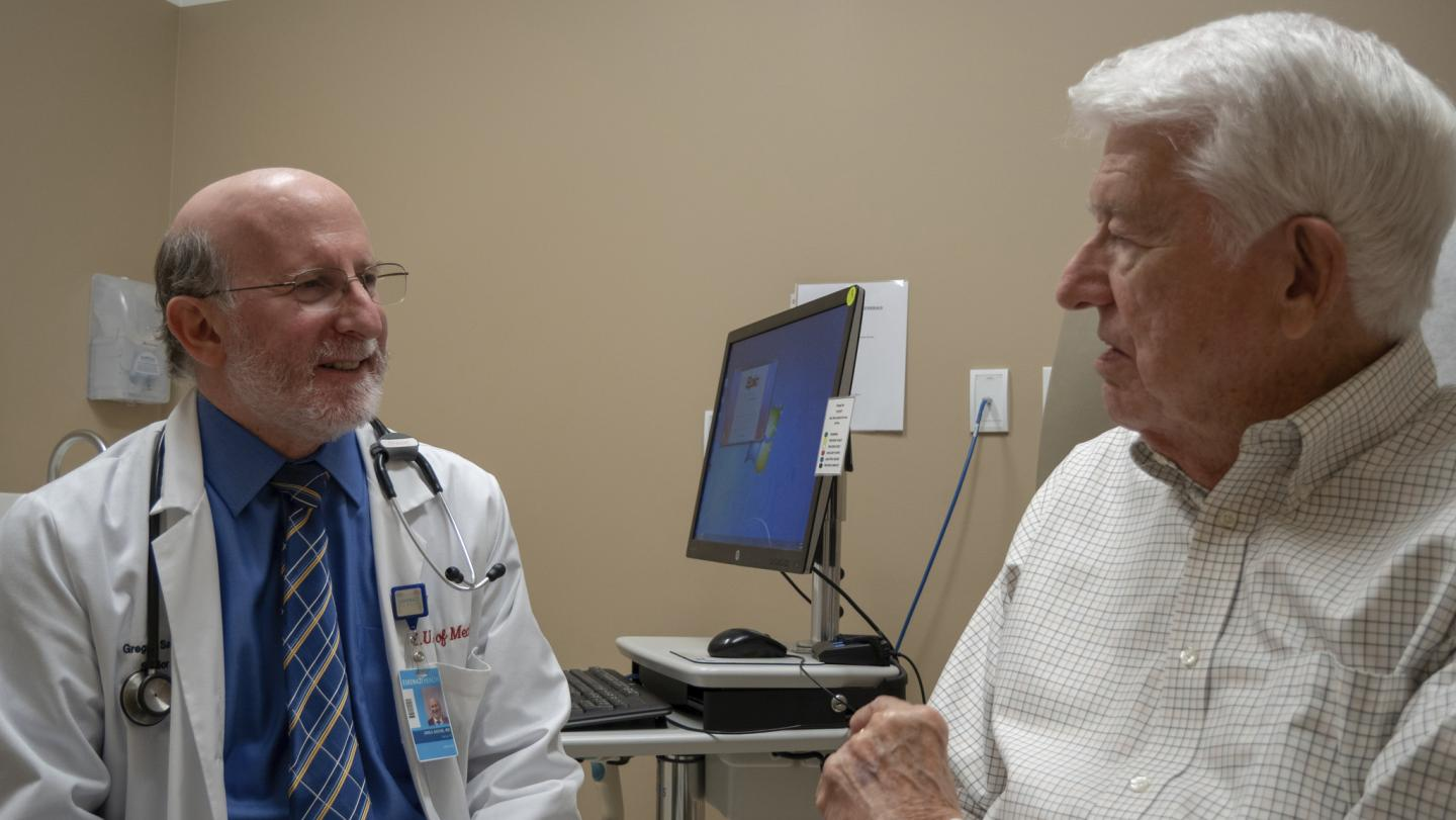 This is an image of Regenstrief Institute investigator Greg Sachs, MD with a patient